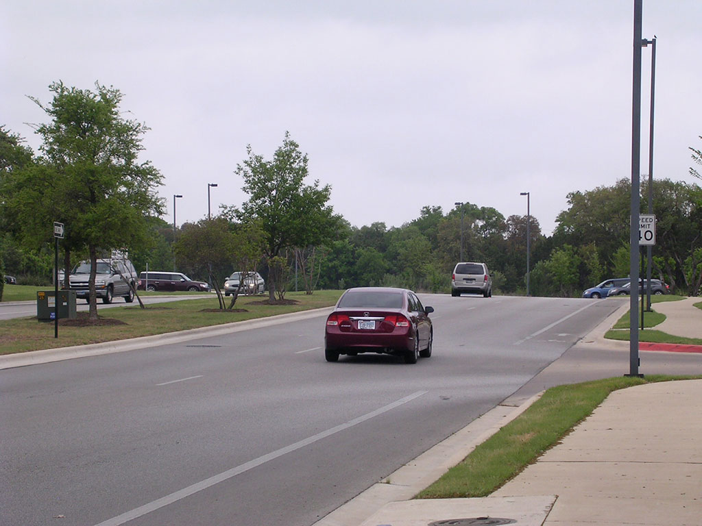 The car in the picture is going past the first parking lot entrance. The one in question is farther up the hill, where cars are coming out on the right.